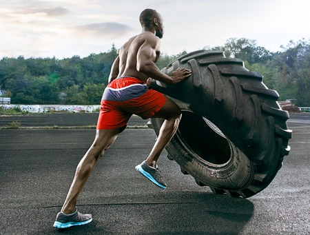 Handsome african american muscular man flipping big tire outdoor. Banco de Imagens
