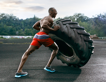 Handsome african american muscular man flipping big tire outdoor. Stock Photo