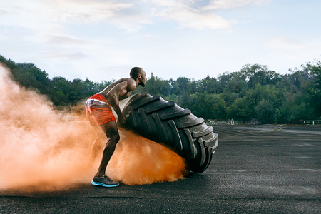 Handsome african american muscular man flipping burning big tire outdoor with smoke