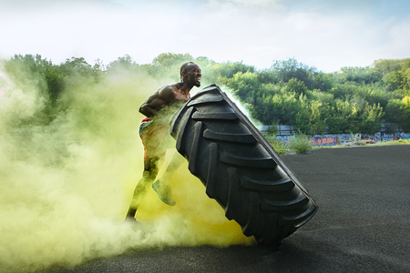 Handsome african american muscular man flipping burning big tire outdoor with smoke Banco de Imagens