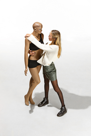 Fashion woman body. The woman hugging mannequin at studio. The hugging day concept