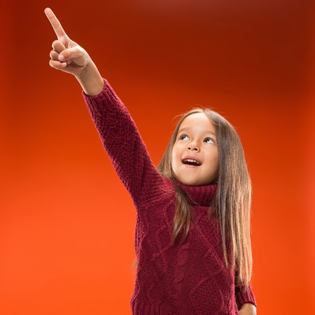 Wow. Beautiful female half-length front portrait isolated on studio backgroud. Young emotional surprised teen girl standing and pointing up. Human emotions, facial expression concept. Trendy colors