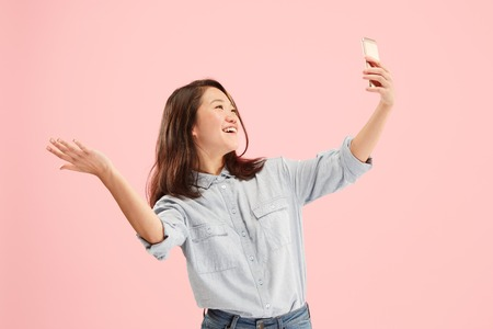 Portrait of a confident happy smiling casual girl making selfie photo by mobile phone isolated over pink background.