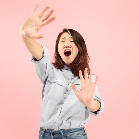 Im afraid. Fright. Portrait of the scared woman. Business woman standing isolated on trendy pink studio background. Female half-length portrait. Human emotions, facial expression concept. Front view 스톡 콘텐츠