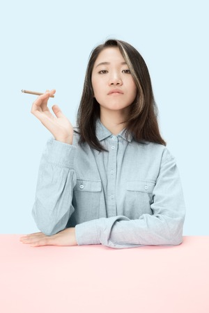 Handsome young korean women smoking cigar while sitting at table at studio. Trendy colors