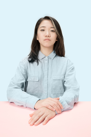 Serious business woman sitting at table, looking at camera isolated on trendy blue studio background. Beautiful, young face. Female half-length portrait. Human emotions, facial expression concept.