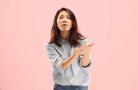 Argue, arguing concept. Beautiful female half-length portrait isolated on pink studio backgroud. Young emotional surprised woman looking at camera.Human emotions, facial expression concept. Front view