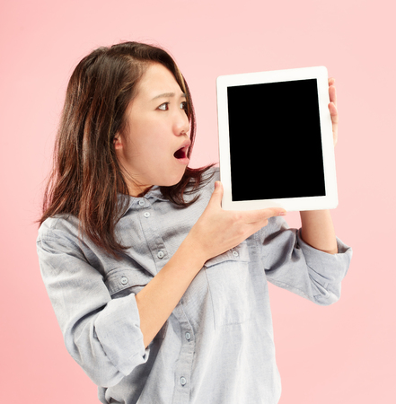 Portrait of a confident casual girl showing blank screen of laptop isolated over pink background.