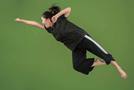 I am happy. Mid-air shot of pretty smiling young woman jumping and gesturing against green studio background. Banco de Imagens