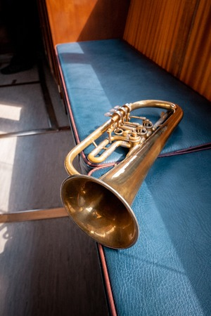 Blowing brass gold wind instrument on the bench