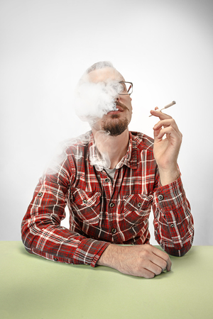 Handsome hipster man smoking cigarette and sitting at table at home or studio. Man looking upwards and enjoying spending free time. Stock Photo