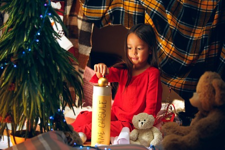 Merry Christmas and Happy Holidays. Cute little child girl writes the letter to Santa Claus near Christmas tree at home indoor. The holiday, childhood, winter, celebration concept