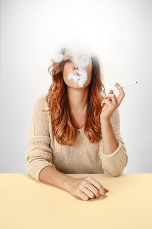 Tranquil woman sitting and smoking at the table. Cloud of smoke covering her face. Copy space. Isolated on white background. Trendy colors