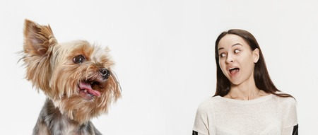 The surprised woman and her dog over white background. Yorkshire terrier at studio against a white. The concept of same emotions