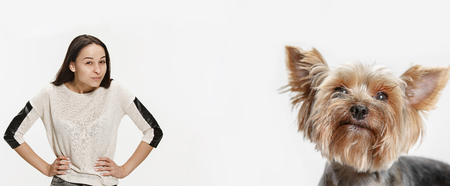 The happy smiling woman and her dog over white background. Yorkshire terrier at studio. The concept of same emotions
