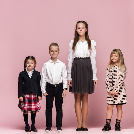 Cute smiling happy stylish children on pink background. Beautiful stylish teen girls and boy standing together and posing at studio. Classic style. Kids fashion and emotions concept.