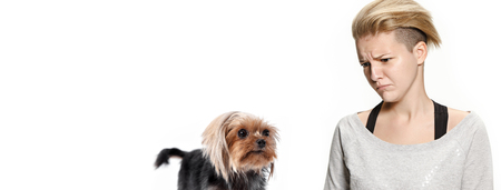 The funny sad woman and her dog looking regretfully over white background. Yorkshire terrier at studio. The concept of humans and animals same emotions