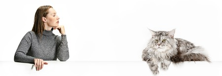 The funny woman and her cat looking serious over white background. The concept of humans and animals same emotions 写真素材