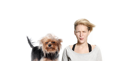 The funny woman and her dog with tongues sticking out over white background. Yorkshire terrier at studio. The concept of humans and animals same emotions