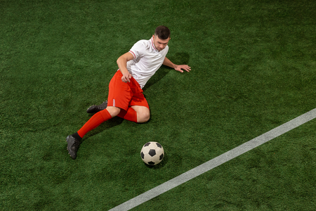 Football player tackling for ball over green grass background. Professional football soccer player in motion at studio. Fit jumping man in action, jump, movement at game.