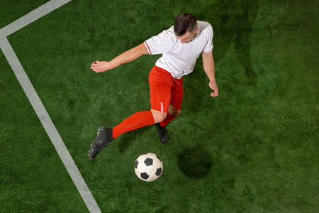 Football player tackling for ball over green grass background. Professional football soccer player in motion at studio. Fit jumping man in action, jump, movement at game. 免版税图像