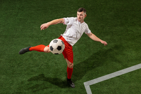 Football player tackling for ball over green grass background. Professional football soccer player in motion at studio. Fit jumping man in action, jump, movement at game. Фото со стока