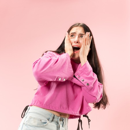 Im afraid. Fright. Portrait of the scared woman. Business woman standing isolated on trendy pink studio background. Female half-length portrait. Human emotions, facial expression concept