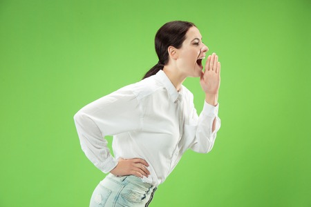 Do not miss. Young casual woman shouting. Shout. Crying emotional woman screaming on green studio background. Female half-length portrait. Human emotions, facial expression concept. Trendy colors