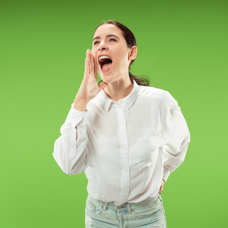 Do not miss. Young casual woman shouting. Shout. Crying emotional woman screaming on green studio background. Female half-length portrait. Human emotions, facial expression concept. Trendy colors Reklamní fotografie - 110928470