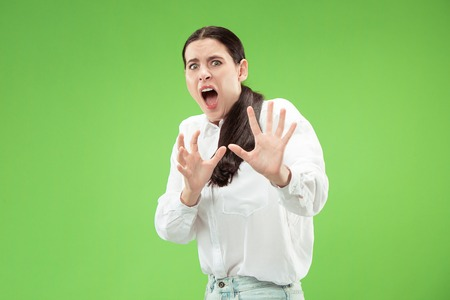 Im afraid. Fright. Portrait of the scared woman. Business woman standing isolated on trendy green studio background. Female half-length portrait. Human emotions, facial expression concept