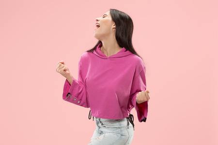 I won. Winning success happy woman celebrating being a winner. Dynamic image of caucasian female model on pink studio background. Victory, delight concept. Human facial emotions concept. Trendy colors Stock Photo