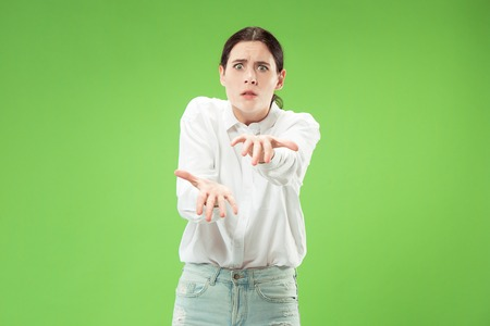 Angry woman looking at camera. Aggressive business woman standing isolated on trendy green studio background. Female half-length portrait. Human emotions, facial expression concept 免版税图像