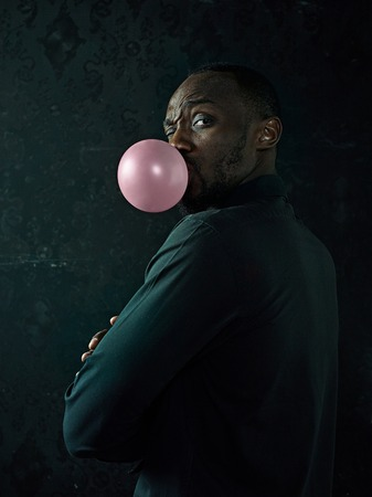 The african american man with bubble gum at studio over dark