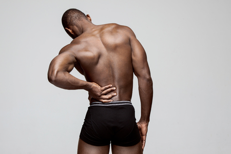 Young man with back pain isolated on gray studio