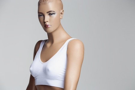 The female mannequin in white underwear over gray studio background. The woman body, fit figure, fitness, diet, sports, plastic surgery and healthy lifestyle concept.