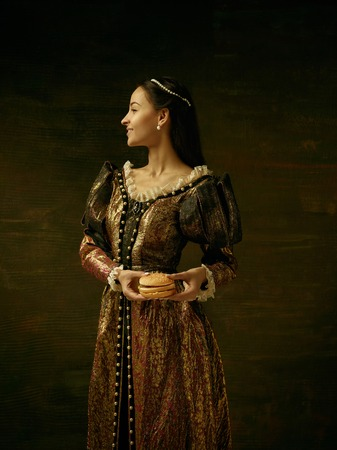 Girl in medieval beautiful dress or costume of the countess at dark studio.