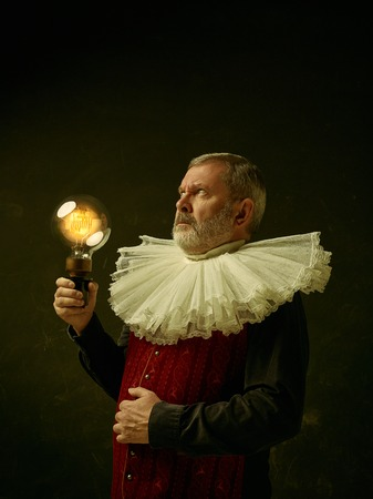Official portrait of historical governor from the golden age with corrugated round collar and retro lamp. Studio shot against dark wall. Stock Photo