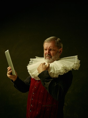 Official portrait of unhappy historical governor from the golden age with corrugated round collar and laptop. Studio shot against dark wall. Stock Photo