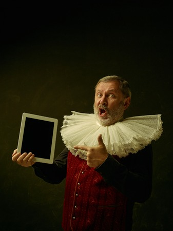 Official portrait of surprised historical governor from the golden age with corrugated round collar and showing screen of laptop. Studio shot against dark wall.