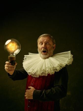 Retrato oficial de gobernador histórico de la edad de oro con cuello redondo ondulado y lámpara retro. Foto de estudio contra la pared oscura. Foto de archivo