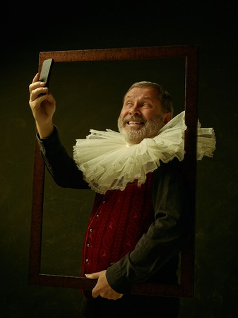 Official portrait of historical governor man with mobile phone from the golden age with corrugated round collar. Studio shot against dark wall. He making selfie photo 写真素材 - 111568838