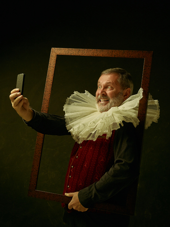 Official portrait of historical governor man with mobile phone from the golden age with corrugated round collar. Studio shot against dark wall. He making selfie photo