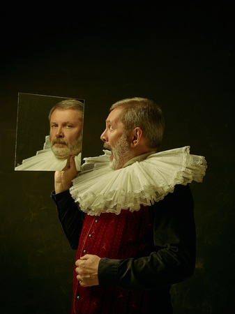 Official portrait of historical governor from the golden age with corrugated round collar and with mirror. Studio shot against dark wall. Archivio Fotografico - 111568918
