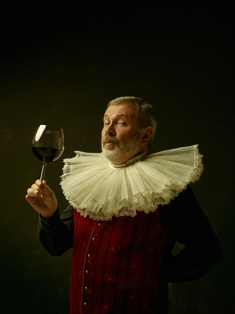 Official portrait of historical governor from the golden age with corrugated round collar with a glass of red wine. Studio shot against dark wall.