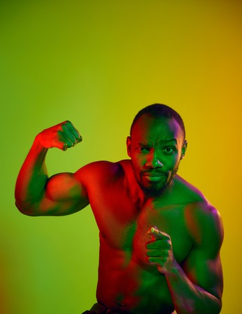 Close up portrait of a young naked angry african man looking at camera. High Fashion male model in colorful bright lights posing in studio. Art design over vivid background.