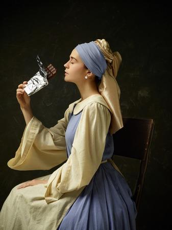 コルセットドレスとボンネットを着た歴史的な衣装を着た中世の女性。暗いスタジオの上に甘いチョコレートバーとツグミの衣装を着て美しい農民の女の子