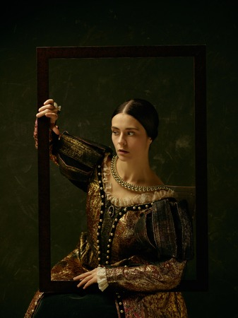 Portrait of a girl wearing a princess or countess dress over dark studio. portrait through picture frame 스톡 콘텐츠 - 111569005