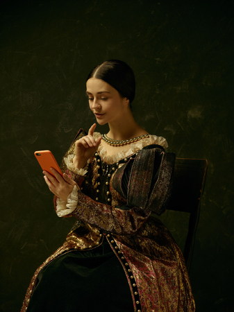 Portrait of a girl wearing a princess or countess dress with mobile phone over dark studio making selfie photo