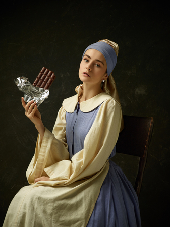 Medieval woman in historical costume wearing corset dress and bonnet. Beautiful peasant girl wearing thrush costume with sweet chocolate bar over dark studio Stock Photo