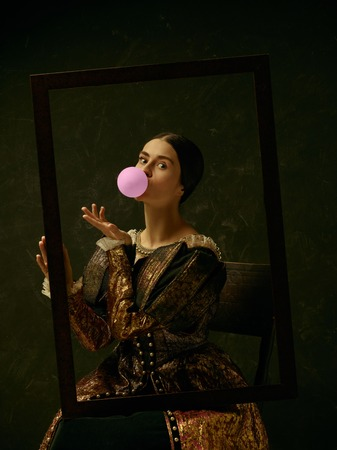 Portrait of a girl wearing a princess or countess dress over dark studio. portrait through picture frame with bubble gum